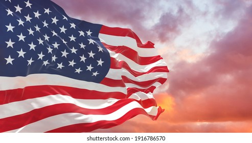Flag of United States of America being waved in the breeze against a sunset sky. US flag
