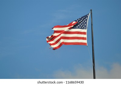 The flag of the United States of America blowing in the wind against a bright blue sky.