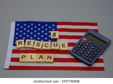 A flag of the United States of America with a dollar sign and a wooden inscription, rescue plan,with a calculator nearby. Concept of economic stimulus, against the recession