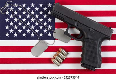 Flag of the United States of America with military identification tags, neck chain, pistol and bullets. Protection concept.