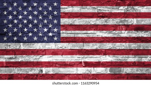 Flag of United States of America over an old brick wall background, surface. American national flag on a brick wall.