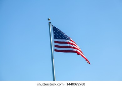 Flag of the United States of America, photograph in the wind, consists of 7 red bands and 6 white bands and a blue rectangle with 50 stars, symbolizing the states of the country.