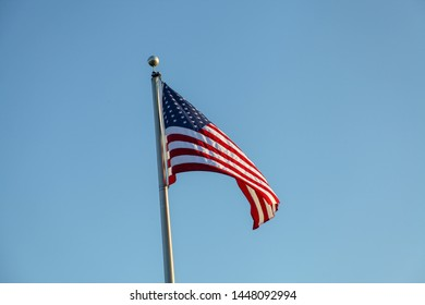 Flag of United States of America, photographed in the wind, fluttering, consisting of 7 red and 6 white bands and a blue rectangle with 50 stars, symbolizing the states of the country.