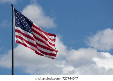 Flag of United States of America (USA) waving in the wind with blue sky and clouds on background