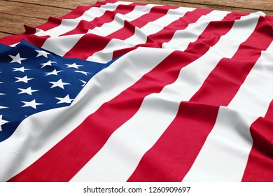 Flag of United States on a wooden desk background. Silk American flag top view.