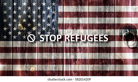 Flag of the United States painted on an old wooden door. Next to the door handle text Stop Refugees.