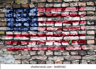 Flag of USA painted on an old brick wall with small ivy plant growing out of a crack.