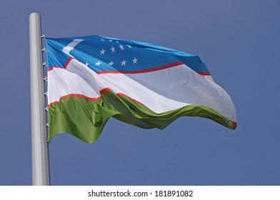 flag of Uzbekistan over blue sky