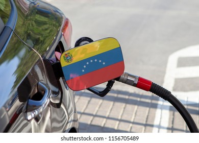 Flag of Venezuela on the car's fuel tank filler flap. Fueling car with petrol pump at a gas station. Petrol station. Gasoline and oil products. Close up.