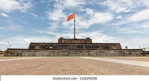 Flag of Vietnam over a tower of the Citadel on blue sky background. Within the Citadel is the Forbidden City. Hue, Vietnam