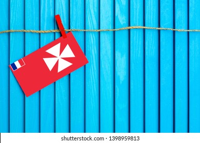 Flag of Wallis And Futuna hanging on clothesline attached with wooden clothespins on aqua blue wooden background. National day concept.