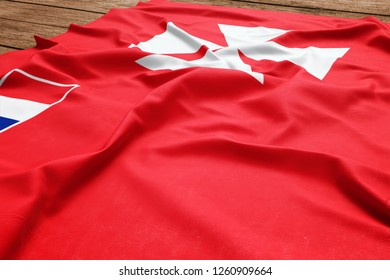 Flag of Wallis And Futuna on a wooden desk background. Silk flag top view.