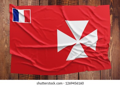 Flag of Wallis And Futuna on a wooden table background. Wrinkled flag top view.