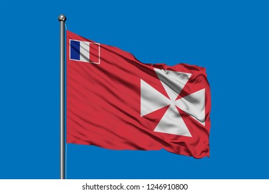 Flag of Wallis and Futuna waving in the wind against deep blue sky.