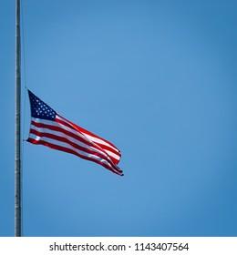 A flag in Washington DC at half mast on a windy day.