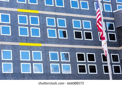 Flag and Windows at Healthcare medical hospital showing blue sky reflection