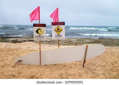flaged high surf, strong curent warning signs with rescue surfboard alone tourest island beach area