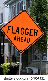 Flagger Ahead sign right in front of homes in small town.