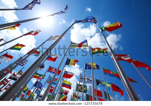 Flaggen aller Nationen der Welt fliegen in blausonnigem Himmel