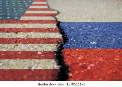 Flags of America and Russia on asphalt are separated by a crack.