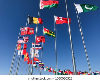 Flags of Belarus, Belgium, Bermuda, United States, Turkey, Thailand, Tonga Pakistan and many others waving in Pyeongchang, South Korea in front of a blue sky in February 2018