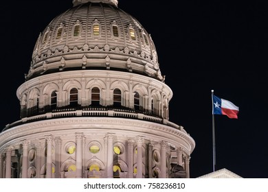 Flags blow in the wind after night falls on the state capital grounds in Austin