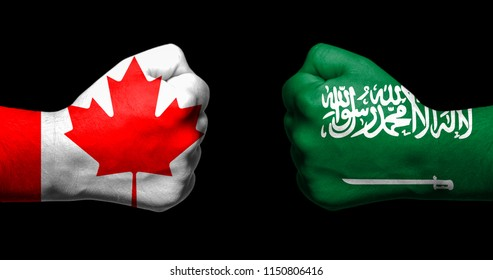 Flags of Canada and Saudi Arabia painted on two clenched fists facing each other on black background/Canada and Saudi Arabia relations concept