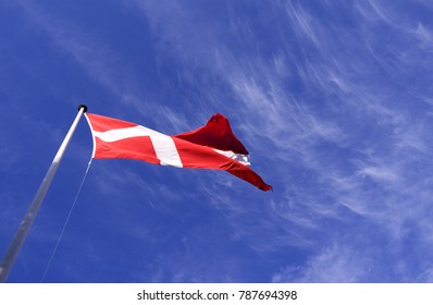 Flags / Denmark: The Danish national flag Dannebrog is fluttering in the gusty coastal wind on Laesoe island