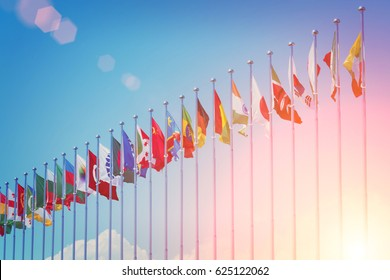 Flags of different countries on the background of the blue sky in the sunlight