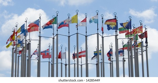 flags of different countries on cloudy blue sky background