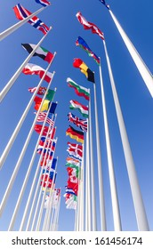 Flags of different countries on flagpoles against the clear blue sky