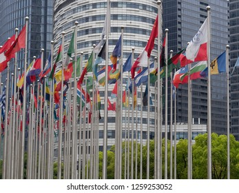 Flags of different countries on flagstaffs in front of modern Architecture in Shanghai