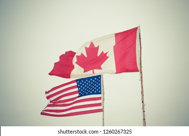 Flags of different USA and Canada on the background of the gloomy sky. Toned.