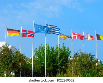 Flags of EU, Greece, Germany, Norway, Sweden, Denmark, France above green trees in blue sky.