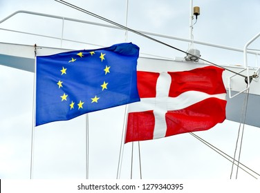 The flags of the EU and the state of Denmark side by side on a mast of a ship