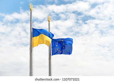 Flags of Europe and Ukraine on the poles with blue sky as background