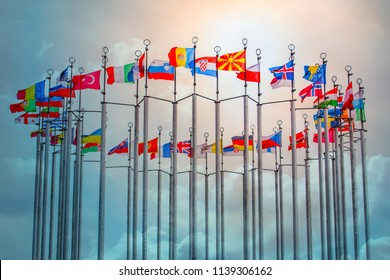 Flags of European states on flagpoles against blue sky background.