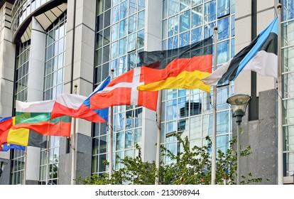 Flags of European Union countries waving near modern European Parliament building in Brussels, Belgium