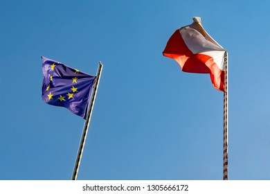 Flags European Union and Poland. Two flags on the background of a beautiful blue sky and green trees.
