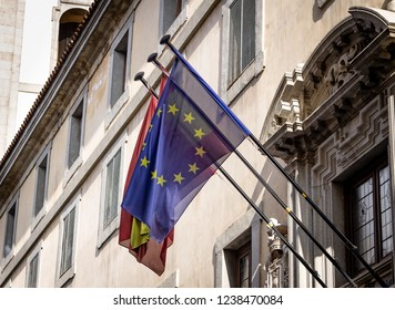 The flags of the European Union and Spain are raised on a balcony from a government building in Madrid, Spain.