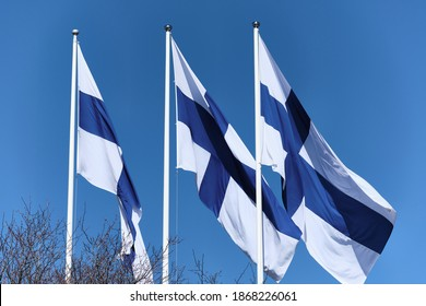 Flags of Finland on the white flagpoles against a blue sky.