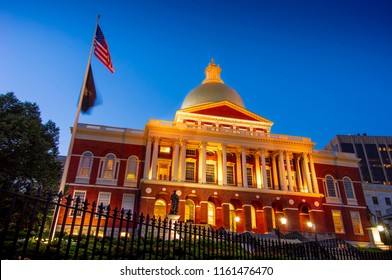 Flags flying during time exposure in front of brick domed Massachusetts State House a dusk why lights illuminating structure in yellow glow.