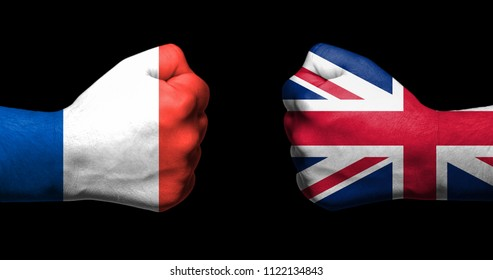 Flags of France and Unied Kingdom painted on two clenched fists facing each other on black background/France-UK relations concept