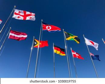 Flags of Georgia, Latvia, North Korea (Peoples Republic), East Timor, Germany, Jamaica, Japan, Denmark, Australia, waving in Pyeongchang, South Korea in front of a blue sky
