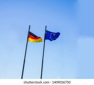 Flags of Germany (Federal Republic of Germany; in German: Bundesrepublik Deutschland) and the European Union (EU) waving in the wind on a bright  blue sky background.