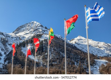 Flags of Greece, Belarus, Lithuania and other countries wave in the wind as a friendship symbol on snowy mountains peak and blue sky background. Various fluttering national flags on flagpoles