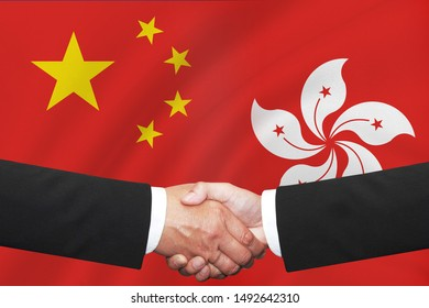 flags of half hong kong with half china  with business handshake