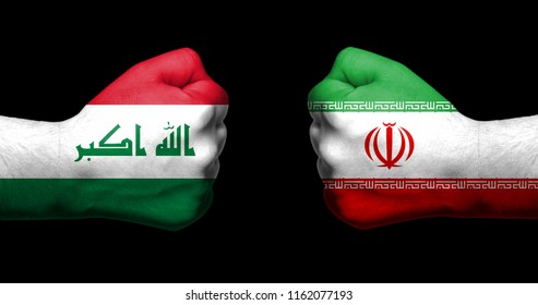 Flags of Iraq and Iran painted on two clenched fists facing each other on black background/Iraq - Iran relations concept
