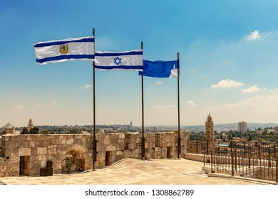 Flags of Israel and of Jerusalem waving on rooftop of the Citadel walls as Tower of David on background in Israel.