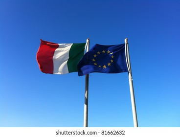 Flags of Italy and Europe waving in the wind on blue sky background